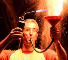 a man is holding a funnel in one hand and igniiting it with a burner in the other hand. a large flame comes out of the funnel to create a huge fire ball above his head.