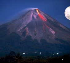 Erupting volcano with full moon in the background
