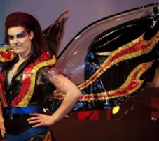 A woman wears a costume made out of car parts that includes huge sparkly wings