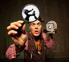 A puppeteer holding a shadow puppet and a camera