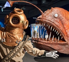 A deep sea diver standing next to a large angler fish with large sharp fish.