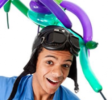 A man wearing overalls and a old leather flying cap with balloons around his head.