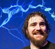 A man with a beard standing in front of electrical sparks.