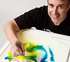 A man painting colour patterns on a flat surface.