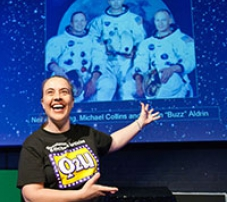 A woman standing in front of a picture of three astronauts.