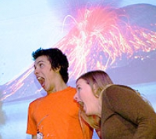 A man and woman standing in front of a picture of a volcano.