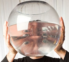 A man looking through a fish bowl full of water.