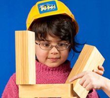 A young girl wearing a toy hard hat and playing with wooden blocks