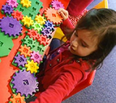 a young girl besides a variety of colourful cogs