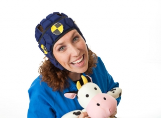 A woman in overalls, wearing a safely crash cap and holding a plush toy cow.