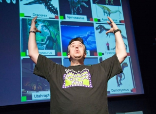 A man with his hands in the air in front of a large screen with various photos of dinosaurs.