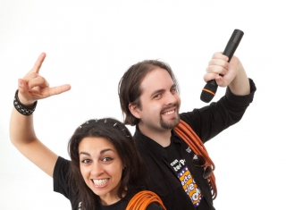 A man and a woman both dressed in roadie gear and each holding a rolled up extension lead, and the man an additional microphone.