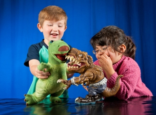 A boy and girl playing with toy dinosaurs