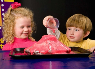 Two young children playing with a model volcano