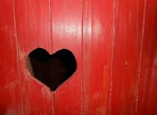 Heart-shaped hole cut in a red wooden wall
